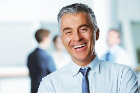 sonrisa: Hombre de negocios maduro con los colegas en el fondo Foto de archivo