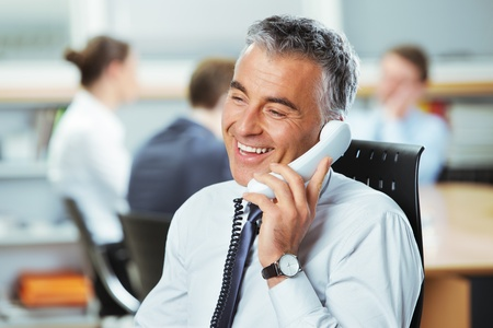 mature business man: Mature businessman at the phone with colleagues in the background