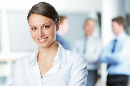 business woman: Happy businesswoman with colleagues in the background