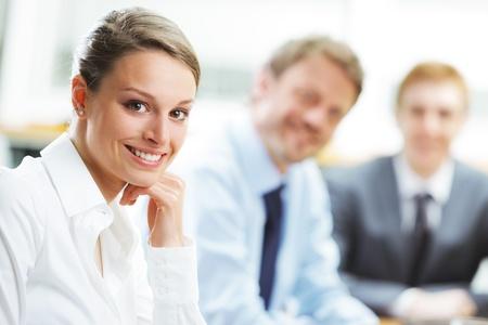 conferencia de negocios: Retrato de una hermosa joven empresaria sonriendo en una reuni�n con sus colegas en el fondo Foto de archivo