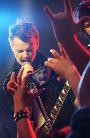 adoring: Guitarist singing on stage at a rock concert for his adoring fans
