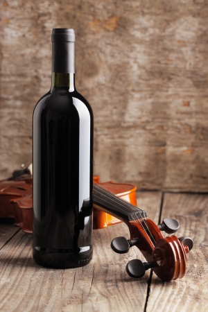 Red wine bottle and violin on wooden background photo