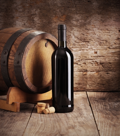 Red wine bottle with barrel and corks photo
