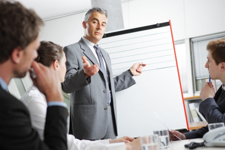 board room: Mature businessman giving a presentation to his colleagues