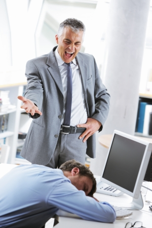 displeased businessman: Tired business man sleeping at work. In the background is angry boss shouting Stock Photo
