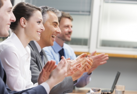 Group of cheerful businesspeople sitting in a row on a presentation and clapping Stock Photo
