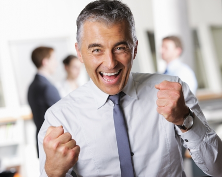 middle aged: Happy mature business man celebrating his success
