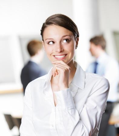 donna pensiero: Bella giovane imprenditrice pensare, guardando in alto