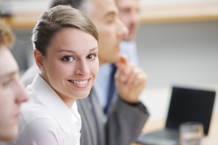 Portrait of a pretty young businesswoman sitting at a business meeting with colleagues photo