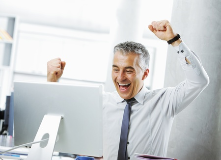Happy mature businessman in office arms raised. Stock Photo - 20143091