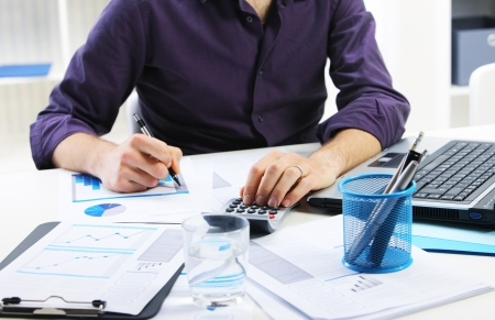 Business man checking financial data on calculator. Stock Photo