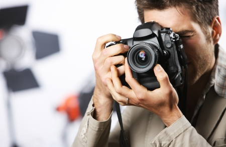 Young man taking photo with professional digital camera, focus on hand and lens Stock Photo