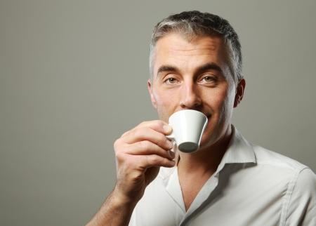 hombre tomando cafe: Hombre maduro hermoso que disfruta de una bebida caliente