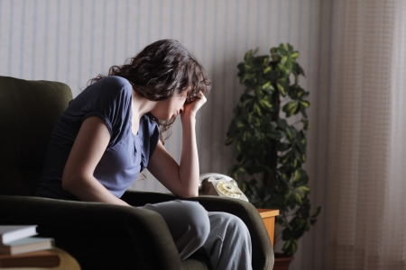 relationship problems: Depressed young woman sitting in chair at home