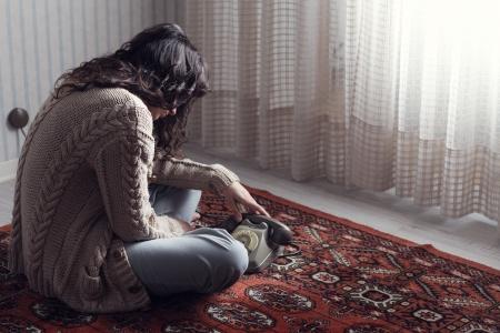 persona deprimida: Triste mujer sentada en el suelo esperando la llamada de tel�fono