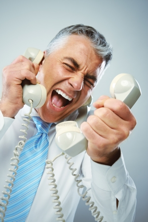 A stressed businessman yells loudly into the three handsets that he is holding.