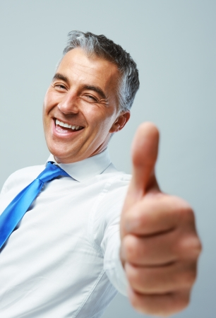 mature businessman: Happy mature business man showing thumbs up sign