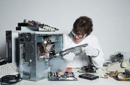 Crazy computer technician is trying to repair a computer with a drill Stock Photo - 20143169