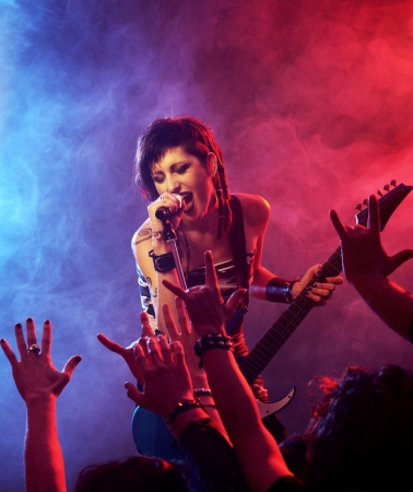 rock star: Female singer and guitarist playing guitar at a rock concert