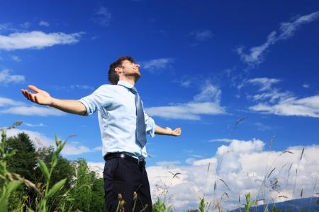 aire puro: Hombre de negocios joven que goza del aire fresco en un día soleado