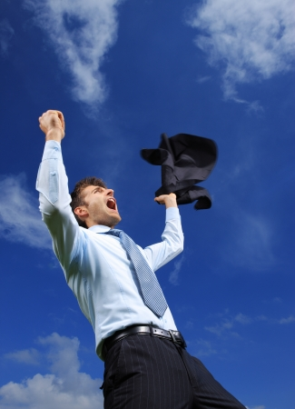 Young business man celebrating his success with arms raised against blue sky photo