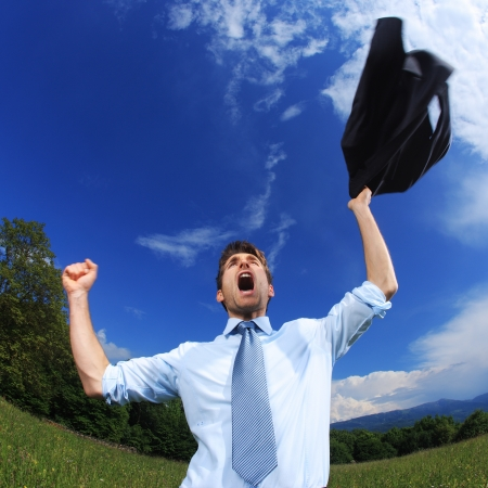 excited man: Young business man celebrating his success with arms raised. Fisheye lens used Stock Photo