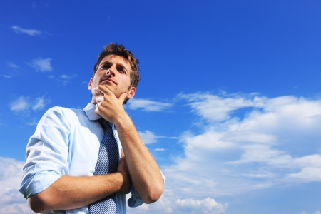 blue sky thinking: Young business man thinking against blue sky Stock Photo