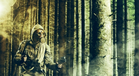 A soldier wearing gas mask is fighting in the forest photo