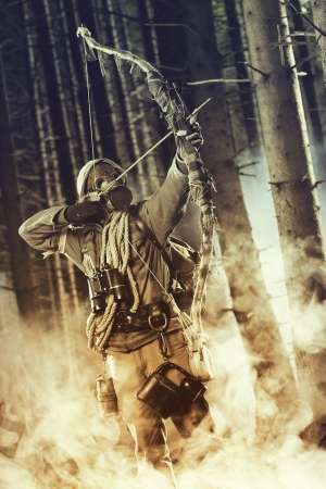 A male bow hunter wearing gas mask, draws back on his bow photo