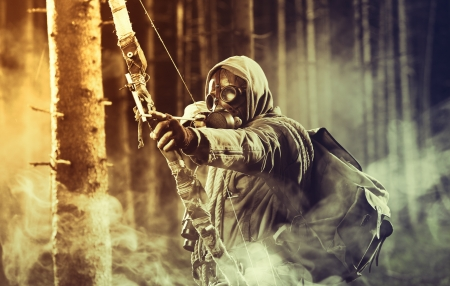 apocalyptic: A male bow hunter wearing gas mask, draws back on his bow Stock Photo