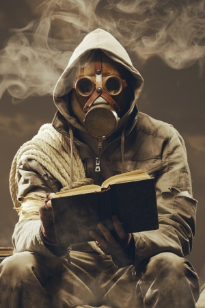 Post apocalyptic survivor in gas mask reading a book photo