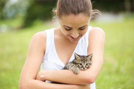 Beautiful young woman embracing a cute kitten outdoors Stock Photo - 20569864