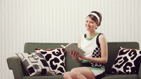 Cheerful girl sitting on the couch with a book Stock Photo - 21510563
