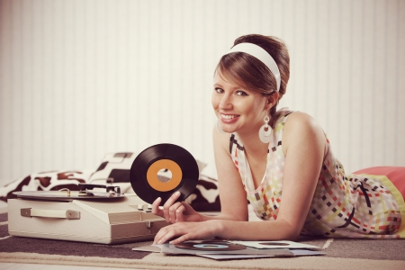 A cheerful young woman listening to a record photo
