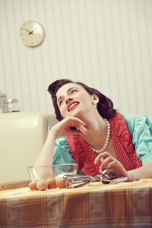 Vintage portrait of a happy housewife in the kitchen photo