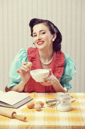 retro housewife: Cheerful housewife cooking in the kitchen