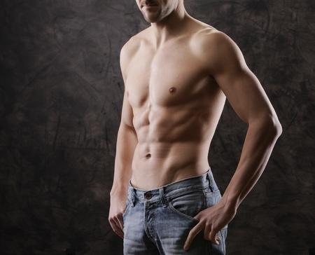 Sexy muscular man on dark background photo