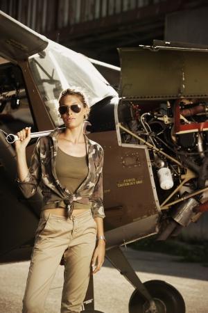 aviator: Woman airplane mechanic. Airplane on the background