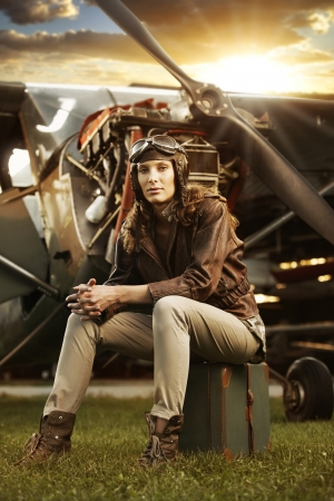 pilot: Portrait of young woman airplane pilot. Airplane on the background