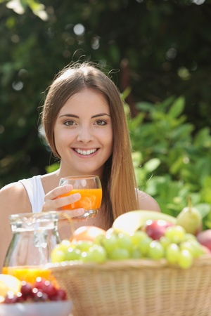Young woman relaxes in the garden drinking a orange juice photo