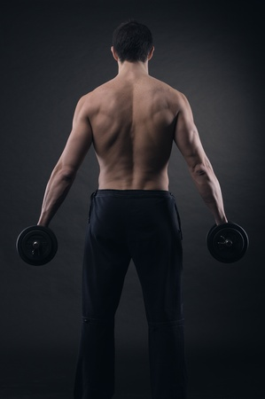 Muscular male athlete is training by lifting dumbbells Stock Photo - 21510647