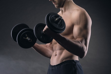 Close up of muscular male athlete is training by lifting dumbbells photo