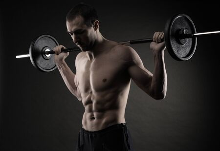 Muscular male athlete is training by lifting the barbell photo