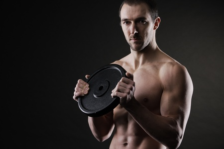 Muscular male athlete with a weight in hands photo