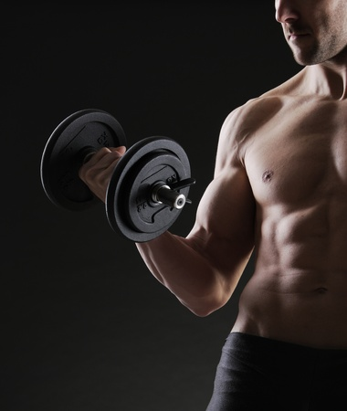 Muscular male athlete is training by lifting dumbbells photo