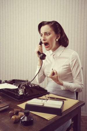 Stressed Young Woman shouting into telephone photo