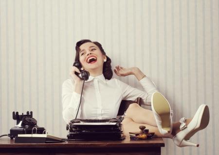 책상에 전화에 얘기하는 쾌활 한 여자 스톡 콘텐츠