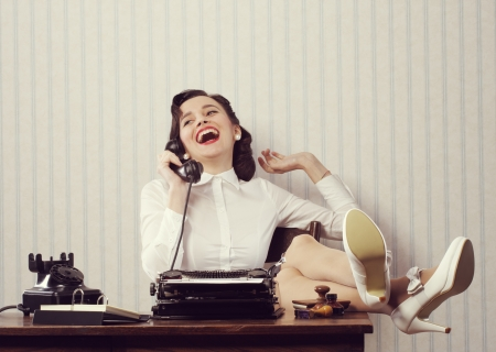 Cheerful woman talking on phone at desk photo