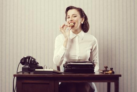 work break: Smiling business woman eating a cookie, break from work