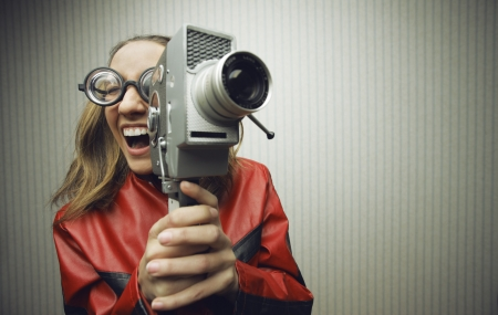古い昔ながらシネ カメラを用いたオタクの女性 写真素材